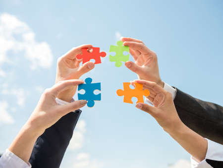 connecting: Closeup of business people wanting to put four pieces of puzzle together. Sky background.