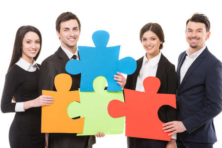 Image of four confident business people wanting to put pieces of puzzle together. Team work.