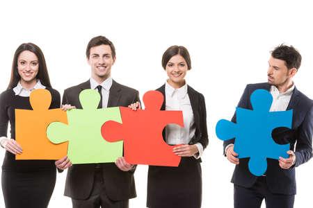 퍼즐 조각을 함께 넣어하고자하는 4 자신감 비즈니스 사람들의 이미지. 팀워크. 스톡 콘텐츠