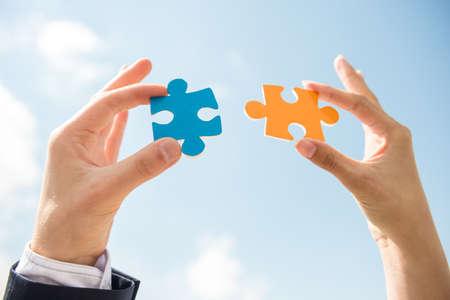 Primer plano de la gente de negocios que quieren poner dos piezas de rompecabezas. Fondo del cielo. Foto de archivo - 40755584
