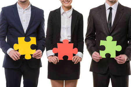 put together: Close-up of business people wanting to put pieces of puzzle together.