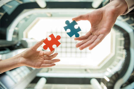 put together: Close-up of business people wanting to put two pieces of puzzle together.