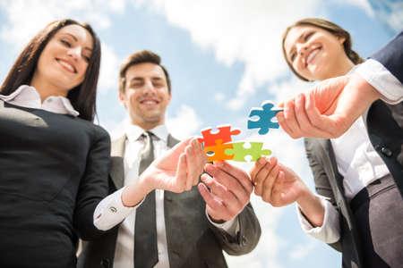 パズルの 4 つの作品を一緒にしたいビジネスの方々 のクローズ アップ。チームの仕事。