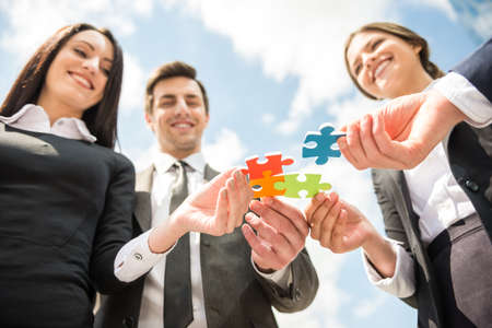 pieces: Closeup of business people wanting to put four pieces of puzzle together. Team work. Stock Photo
