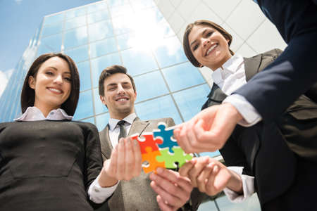 wanting: Closeup of business people wanting to put four pieces of puzzle together. Team work. Stock Photo