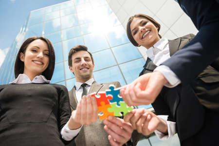 Nahaufnahme der Geschäftsleute wollen vier Puzzleteile zusammenzufügen. Teamarbeit.