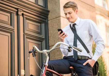 bicicleta: Joven trabajador de oficina apuesto que va a trabajar en su bicicleta. Concepto de estilo de vida saludable. Foto de archivo