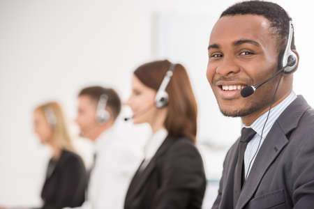 contact center: Group of agents sitting in line in a bright call centre. Stock Photo
