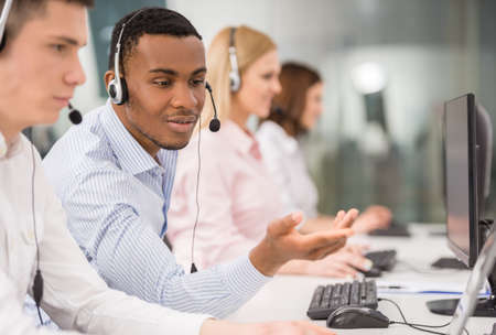 help center: Phone operator working at call centre office helping hiss colleague. Stock Photo
