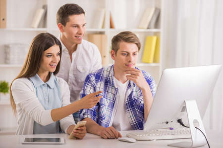 programmers: Group of young programmers sitting at office room and working on project.