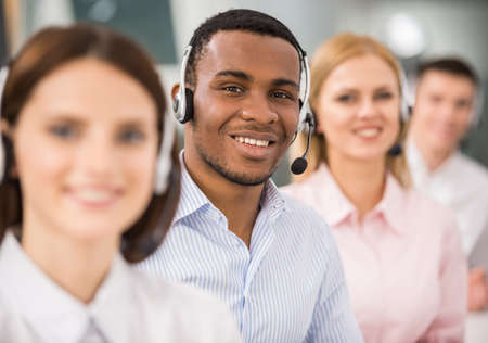 Smiling call center employees sitting in line with their headsets. photo