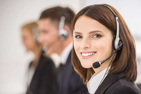 customer service representative: Smiling beautiful lady working at call center with colleagues in office.