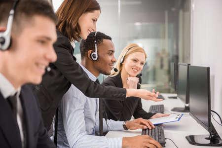 Zijaanzicht van vrouwelijke manager helpen haar personeel in een call center.