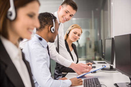 contact center: Manager explaining something to his employee in a call centre. Stock Photo