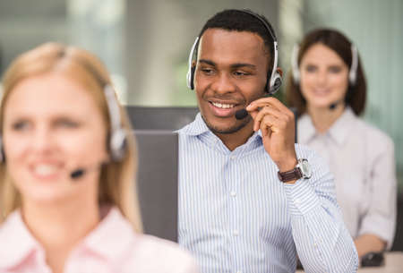 sales agent: Attractive positive young colleagues working in call center office. Side view.