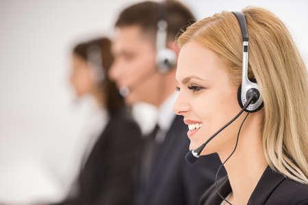 recepcionista: Línea de los operadores de telefonía con auriculares trabajar en la oficina. Vista lateral. Foto de archivo