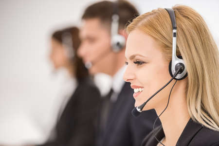 headset woman: Line of phone operators with headsets work at office. Side view.