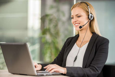 recepcionista: Joven y bella mujer con auriculares sentado en la oficina y el uso de ordenador portátil.