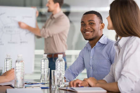 teaching adult: Successful team leader with his team at meeting room. Stock Photo