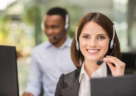Mooie jonge dame praten op de headset op call center office.