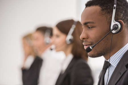 Line of phone operators with headsets work at office. Side view.