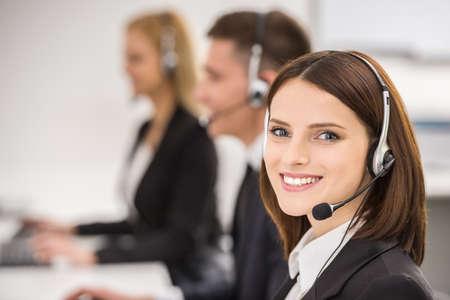 servicio al cliente: Se�ora hermosa sonriente que trabaja en centro de atenci�n telef�nica con sus colegas en la oficina.