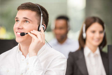 Joyful agent working in a call centre with his headset. Stock Photo - 41409859