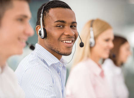 customer service representative: Agent smiling while working on his computer with colleagues next to him.