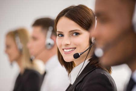 Les travailleurs des centres d'appels de travail en ligne avec leurs casques. Vue de côté.