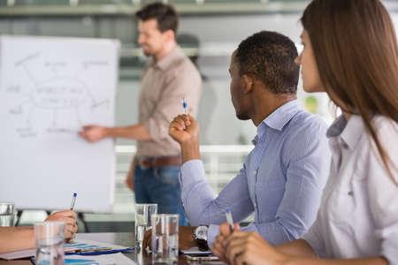 lider: Líder del equipo acertado con su equipo en la sala de reuniones.