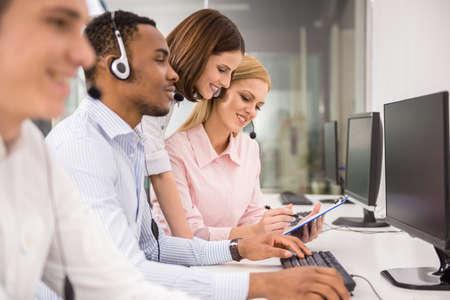servicio al cliente: Gerente ayudando agente de call center femenino hermoso.