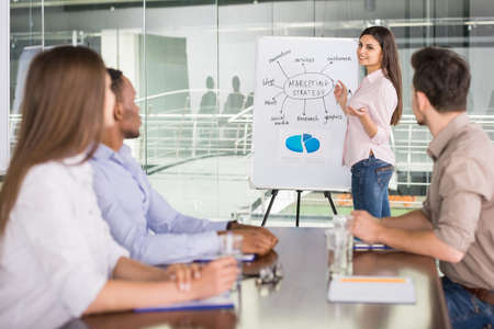 board room: Confident business woman presenting new business strategy at conference room to partners.