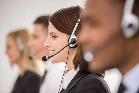 Call center medewerkers werken in lijn met hun headsets. Zijaanzicht. Stockfoto