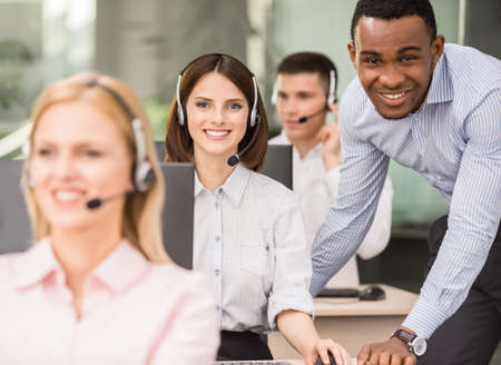 office employees: Manager explaining something to his employee in a call centre. Stock Photo