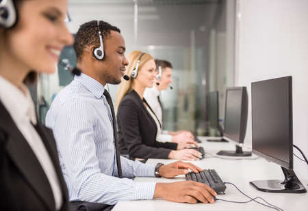 Line of phone operators with headsets work at office. Side view. photo