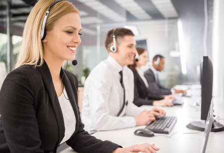 customer service representative: Group of agents sitting in line in a bright call centre. Stock Photo