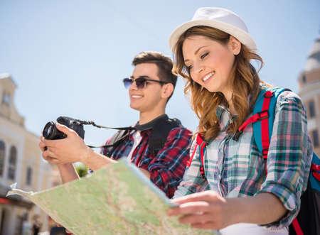 guia de turismo: Pareja de turistas joven con la correspondencia que buscan una manera y haciendo fotos ot la ciudad.