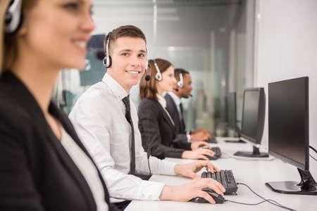 彼の隣に同僚と自分のコンピューターで作業しながら笑みを浮かべてエージェント。