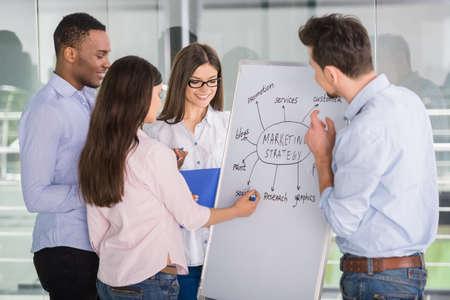 Groupe de jeunes collègues habillé debout occasionnel en bureau moderne et remue-méninges. Banque d'images