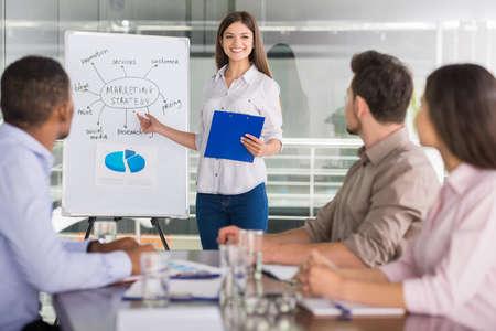 Jonge mensen uit het bedrijfsleven zitten in een vergaderzaal en luisteren luidspreker.