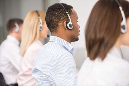 help center: Call centre workers working in line with their headsets. Back view.