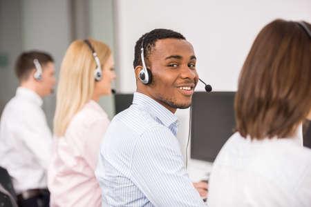 computer center: agente alegre que trabaja en un centro de llamadas con el auricular.