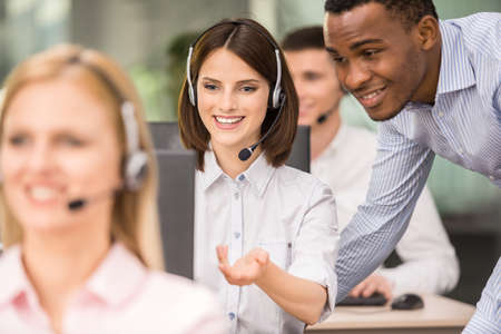 call center woman: Manager explaining something to his employee in a call centre. Stock Photo