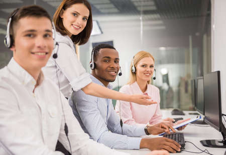 contact center: Beautiful female manager helping call centre agent. Stock Photo