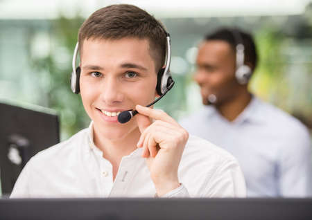 Agent smiling while working on his computer with colleague next to him. Stock Photo
