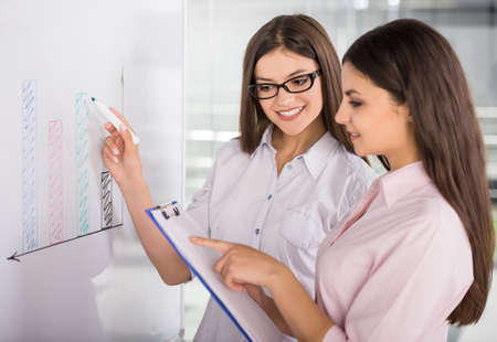 Two beautiful office workers drawing business strategy concept. Stock Photo