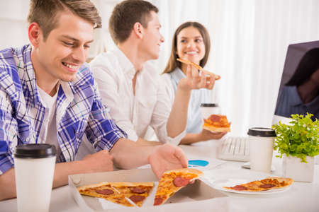 Group of young colleagues sitting at the table, eating pizza and working together. photo