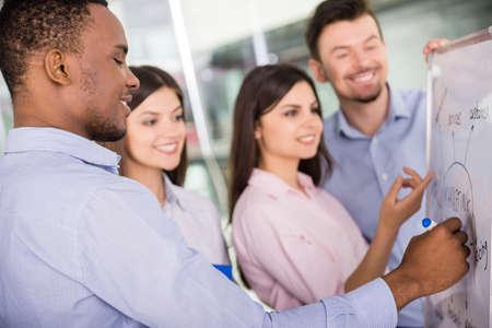 Groupe de jeunes collègues habillé debout occasionnel en bureau moderne et remue-méninges.