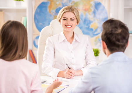 decided: Couple sitting at tourist agency and decided where to travel. Stock Photo