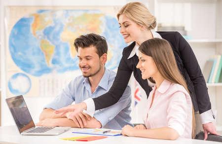 agencia de viajes: Feliz pareja joven que se sienta en la agencia de turismo y hablar con un agente de viajes.